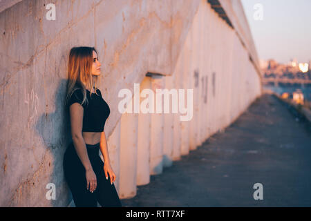 Beautiful smiling fitness woman on city background with copy space. Street portrait of a slender young girl - Stock Photo