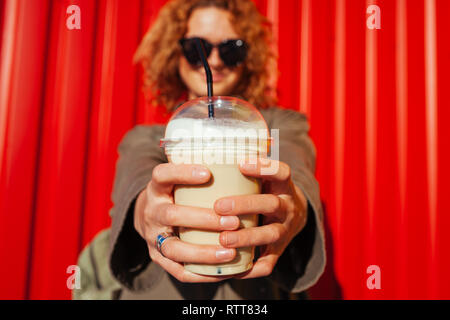 Hipster young woman with curly red hair holding coffee against red wall. Close-up of a drink in plastic cup - Stock Photo