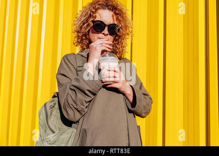 Hipster young woman with backpack drinking coffee against yellow wall. Stylish summer traveller in sunglasses relaxing outdoors - Stock Photo