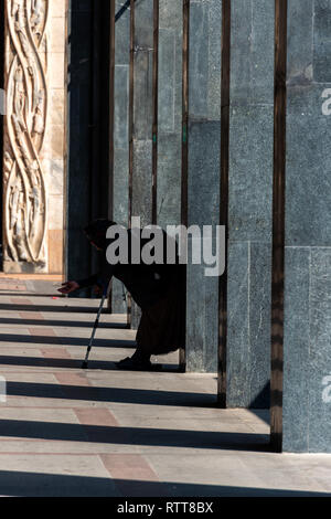 Poor beggar aged female dressed in dark long clothes near the Piazza del Duomo in Milan, Italy - Stock Photo