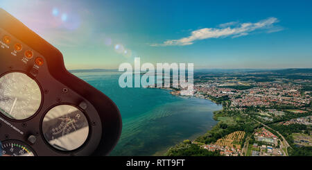 Helicopter cockpit with aerial view on lake and landscape with flares - Stock Photo