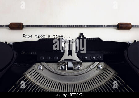 Old retro vintage black typewriter with close-up typing text Once upon a time as heading on aged paper - Stock Photo