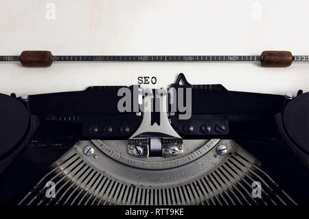 Old retro vintage black typewriter with close-up typing text SEO as heading on aged paper