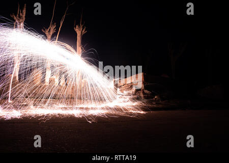 Effect of sparks of incandescent steel. Long exposure photo. light painting technique Fire wall in the abandoned city of Epecuen. - Stock Photo