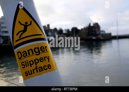 danger slippery, surface, sign, by,the,sea,yellow,black, - Stock Photo