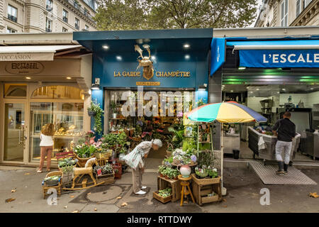 A woman looking at the flower displays at La Garde Champêtre ,a florist shop and flower seller on Rue des Martyrs , St Georges ,Paris - Stock Photo