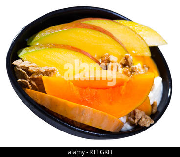 Pumpkin slices bake in the oven, cut the mango. Oat flakes, whipped cream, dried fruits on a plate with pumpkin and mango. Isolated over white backgro - Stock Photo