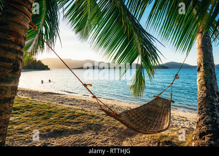 Empty hammock between two palm trees on the beach at sunset. Silhouette of couple in the background in sea. Holiday and vacation concept - Stock Photo