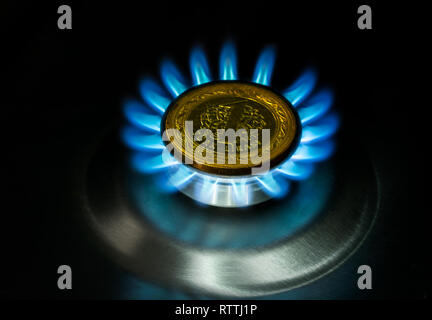 Gas price evolution concept, blue flame and coins ( Turkish coins) - Stock Photo