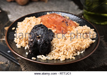 Homemade rice stew with black pudding and tomato in porcelain dish on wood - Stock Photo