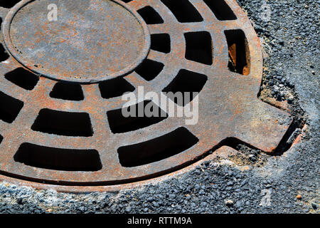 Cast-iron manhole cover storm sewer in the park close-up - Stock Photo