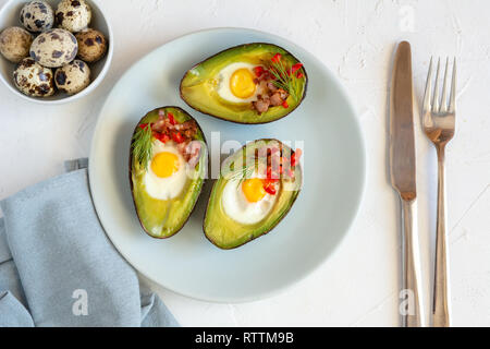 Quail eggs baked in avocado with bacon, red paprika and dill. - Stock Photo