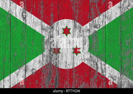 Flag of Burundi painted on worn out wooden texture background. - Stock Photo
