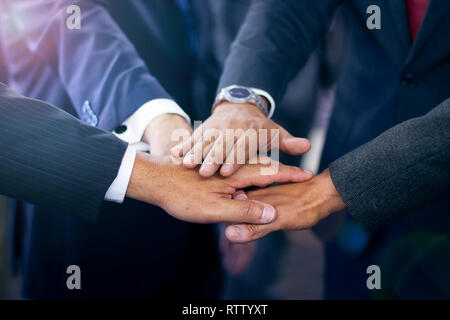 Group of hispanic business people joining hands wearing suits, teamwork and collaboration concept - Stock Photo