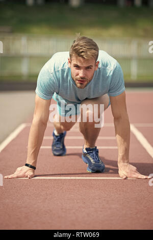 Start of sport career. Man runner on start position stadium background. Sportsman run outdoor at running track. Runner start position running surface. Sportsman on concentrated face ready to go. - Stock Photo