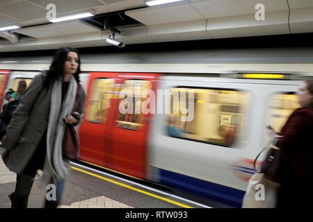 London underground tube train in motion and female passenger walking along platform at Brixton station in South London UK  KATHY DEWITT - Stock Photo