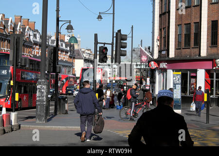 People walking along busy Brixton Road crossing the street at traffic lights and buses in Brixton, Borough of Lambeth, South London UK   KATHY DEWITT - Stock Photo