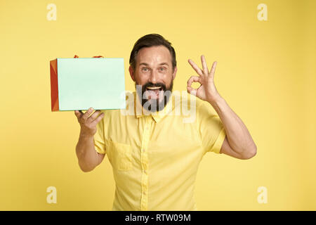 presenting your product. happy man hold shopping bag and presenting product. copy space play for presenting product. man with ok gesture presenting product - Stock Photo