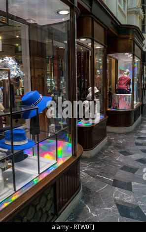 Hat shop window display showing a rainbow effect in the reflections in Burlington Arcade, London, UK - Stock Photo