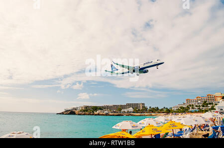 Philipsburg, Sint Maarten - January 24, 2016: jet flight low fly over maho beach. Plane land on cloudy sky. Airplane over people at blue sea. Wanderlust, travel and trip. Beach vacation at Caribbean. - Stock Photo