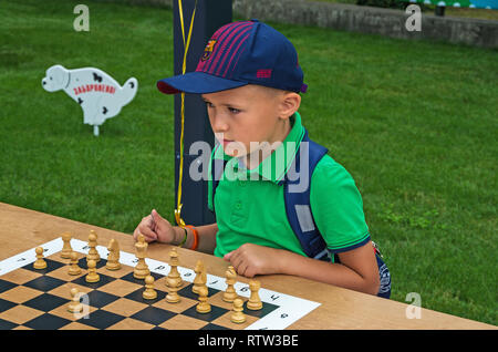 Dnipro, Ukraine - June 27, 2018: Young chess player play chess on day of opening of inclusive city park - Stock Photo