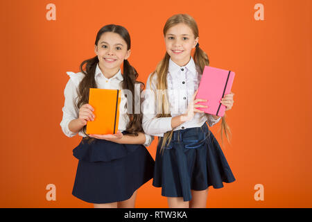Cute pupils. Little children with school diaries for making notes. Cute schoolgirls holding lesson books. School children learn reading books. Small girls classmates with workbooks for writing. - Stock Photo