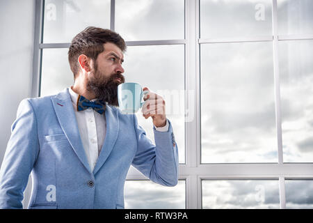 good morning coffee. serious bearded man drink coffee. businessman in formal outfit. modern life. business man at window. future success. morning inspiration. copy space. enjoying morning coffee. - Stock Photo
