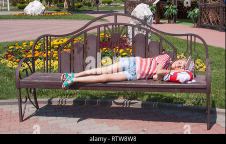 girl resting on a wooden bench in the park   background of  lawn with flowers - Stock Photo