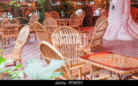 cozy street cafe with wicker furniture - Stock Photo