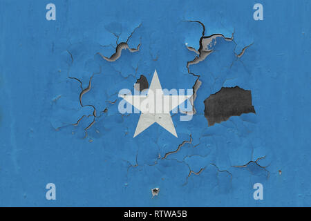 Close up grungy, damaged and weathered Somalia flag on wall peeling off paint to see inside surface. - Stock Photo