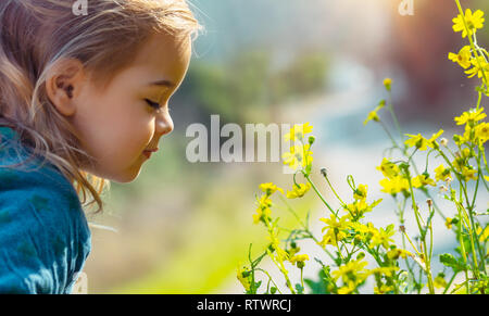Profile portrait of a sweet little baby enjoying flowers aroma, having fun in spring park, beauty and freshness of small yellow wildflowers - Stock Photo