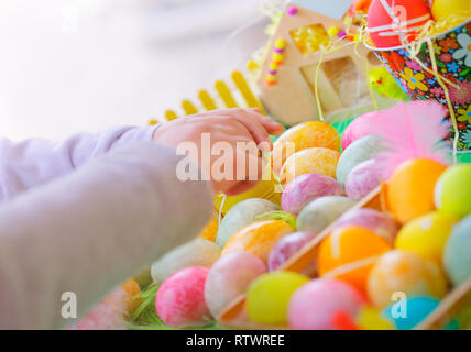 Closeup photo of a colorful painted eggs, child making handmade crafts for great religious holiday, happy Easter tradition - Stock Photo
