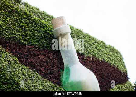 Art Installation of Bottle on the Wall with Plants on Facade. Green Facade with Art Installation. Giant Art Work. - Stock Photo