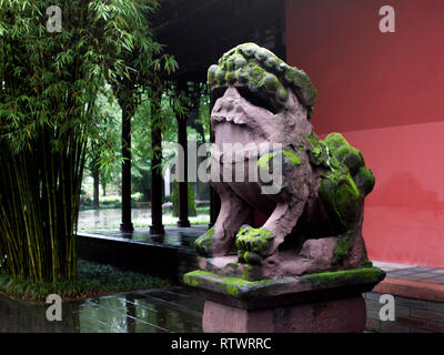 Mossy Stone Lion in front of a Chinese Building with Traditional Architecture Style, next to Bamboo Trees. - Stock Photo