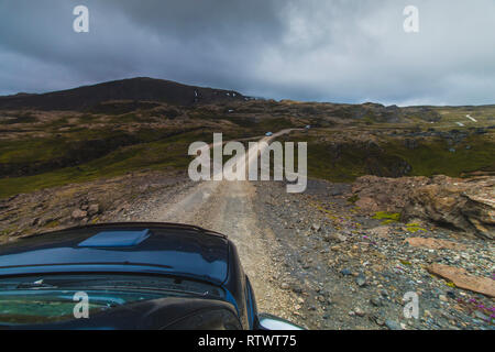 Blue car driving in highlands Iceland view over the car hood at summer time - Stock Photo