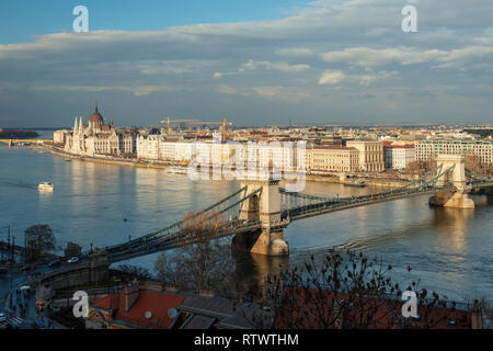 Afternoon in Budapest, Hungary. Chain Bridge across the Danube and Hungarian Parliament visible in the distance. - Stock Photo