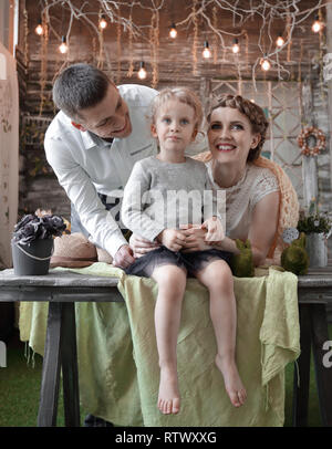 mom ,dad and daughter in the cozy living room - Stock Photo