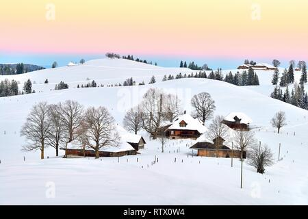Farmhouses in snow-covered hilly landscape in the morning light, Schallenberg, Emmental, Canton Bern, Switzerland - Stock Photo