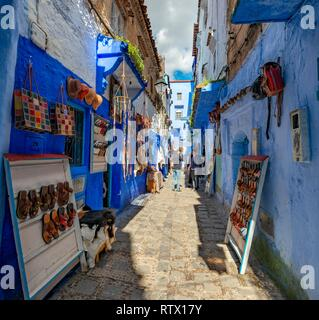 Sale of leather sandals in narrow lane with blue houses, Medina of Chefchaouen, Chaouen, Tangier-Tétouan, Morocco - Stock Photo