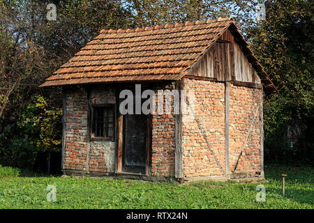 Backyard old red brick storage structure with dilapidated wooden doors and window surrounded with green grass and dense trees in background - Stock Photo