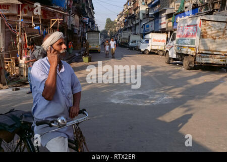 A cyclist in Bhendi Bazar, Mumbai, India, a migrant from the northern state of Uttar Pradesh, stops to take a call on his mobile phone - Stock Photo