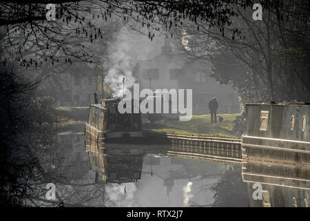 A misty morning on the Trent and Mersey canal at Great Haywood in Staffordshire. The scene shows dog walker and a boat with smoke coming from chimney - Stock Photo
