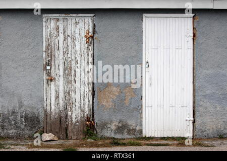 Identical two white wooden doors in different stages from brand new to dilapidated old with cracked boards and faded paint locked with padlocks - Stock Photo