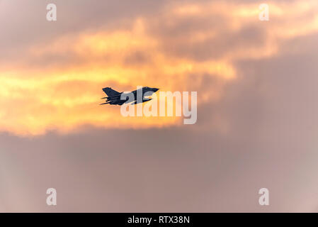 A Royal Air Force Panavia Tornado fighter bomber jet plane passing setting sun as it heads towards retirement. Sun setting on military career - Stock Photo