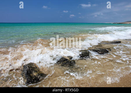 Small sea waves crushing on black rocks at sandy beach, beautiful blue crystal clear water in background. Karpass, Northern Cyprus - Stock Photo