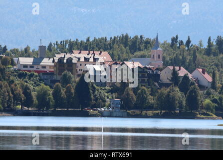 Small mountain town with tall densely built family houses around local church with clear lake in front and dense trees with mountain in background - Stock Photo