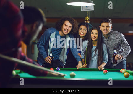 Friends play billiards in bar. - Stock Photo