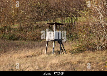 Vintage small wooden dilapidated hunting observation tower with improvised ladders surrounded with high dry grass and dense trees on warm sunny day - Stock Photo