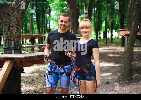 adventure climbing high wire park - hiking in the rope park two young people in safety equipment. - Stock Photo