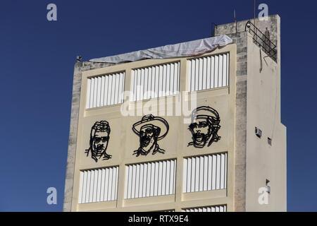 Metal Faces of Fidel Castro, Ernesto Che Guevara and Camilo Cienfuegos on Building Wall Mural near Revolution Museum in old Havana, Cuba - Stock Photo